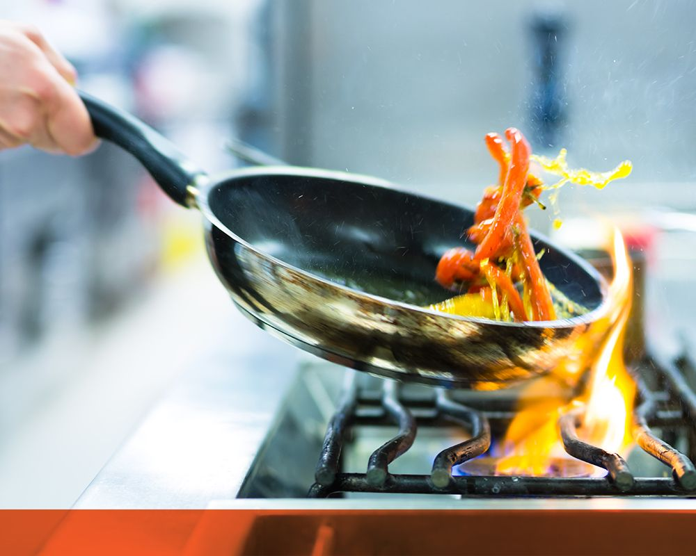 Person stir frying vegetables on commercial stove