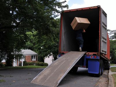 Mover carrying a heavy moving box up a ramp into the back of a moving truck.
