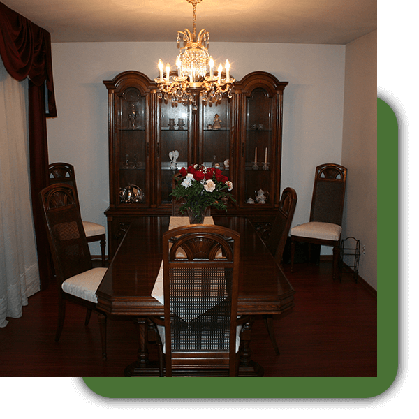 A formal dining room with flowers as a centerpiece.