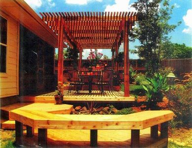 The backyard of a home with deck, built-in seating, and wooden pergola - Americraft Siding & Windows
