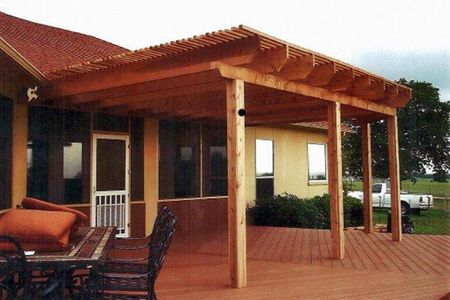 A home with deck, wooden pergola, and seating area - Americraft Siding & Windows
