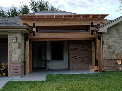A stone house with a wooden two-tiered pergola covering the front porch - Americraft Siding & Windows