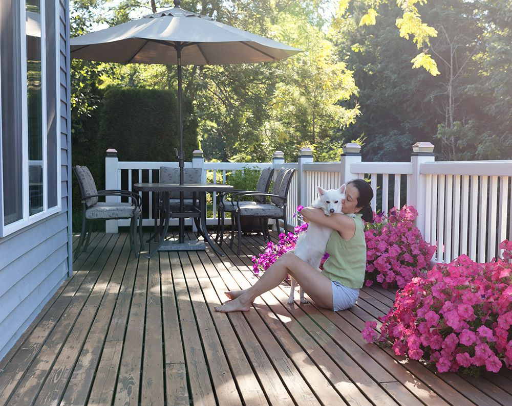Image of a woman on a deck with her dog.