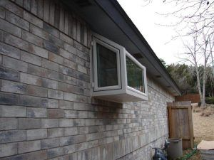 Bay window extending from a brick house - Americraft Siding & Windows