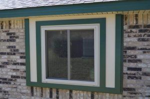 New window on a house with green accents - Americraft Siding & Windows