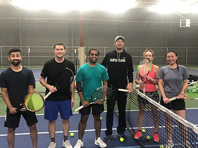 A group of adults playing tennis