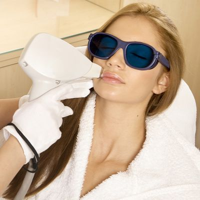 An image of a woman wearing a robe and glasses undergoing a laser treatment