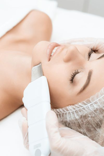An image of a woman undergoing a laser facial treatment in a spa