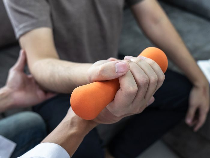 An image of a person lifting a weight with a doctor holding their arm.