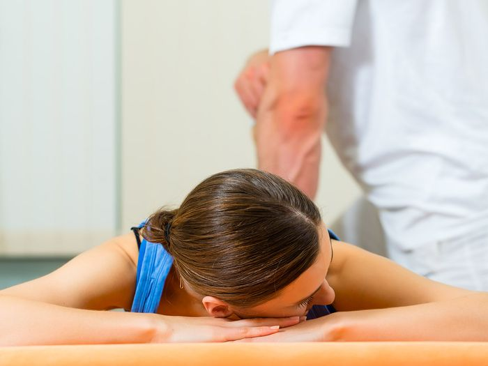Female Patient at the physiotherapy doing physical exercises with her therapist
