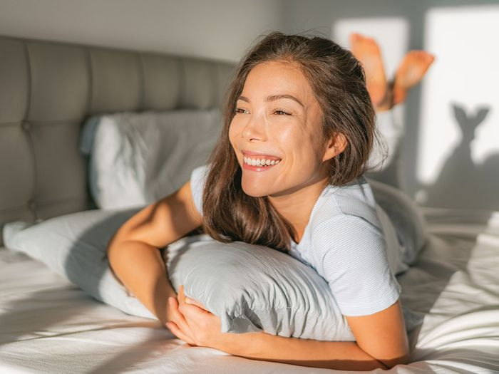 woman waking up early morning happy enjoying sun on comfortable mattress and pillow