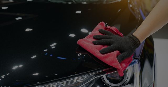Car detailing - the man holds the microfiber in hand and polishes the car. Selective focus
