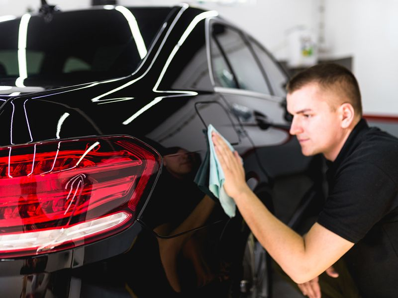 A man cleaning a black car with microfiber cloth as part of car detailing