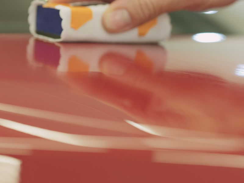 Close up of a hand applying a coating with a sponge to a shiny, reflective red car hood