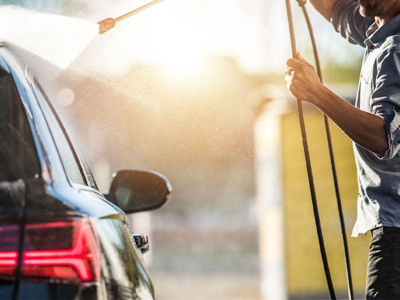 An image of someone washing a black car.