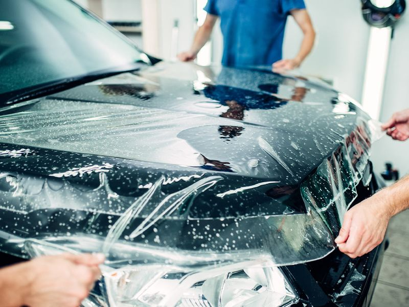 Automotive workers wrap car hood in protective coating for paint protection detailing service.