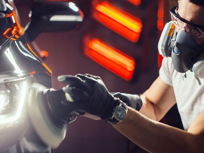 An image of an auto technician polishing a black car with a buffer machine.