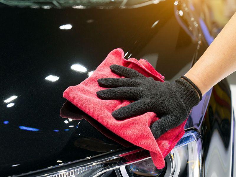 An auto technician wearing a black glove polishing a shiny black car with a red cloth.