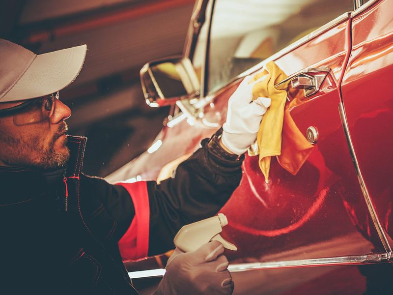 A male technician detailing a red car's door handle