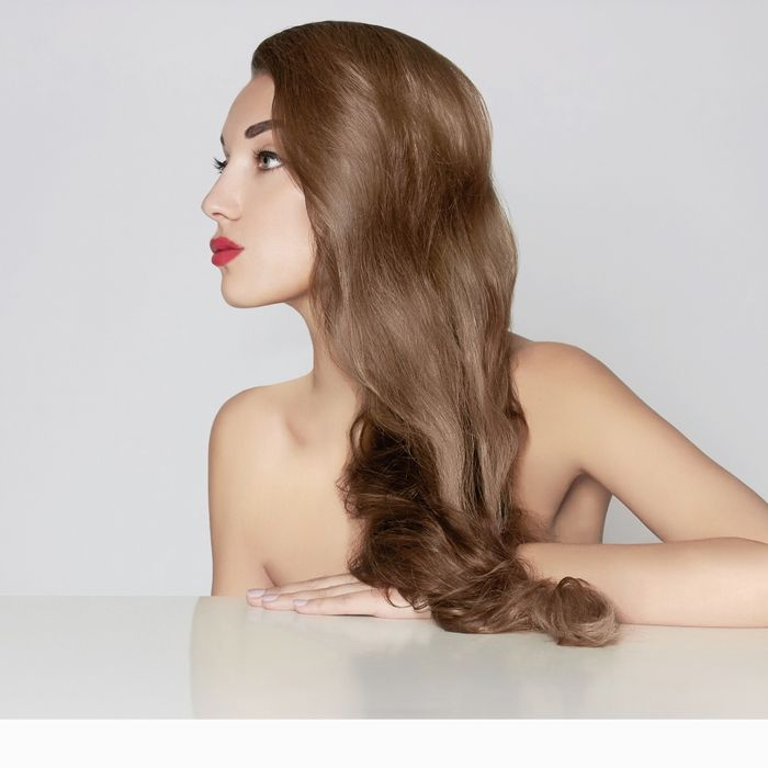 Mannequin with makeup, lipstick, and long brown hair.