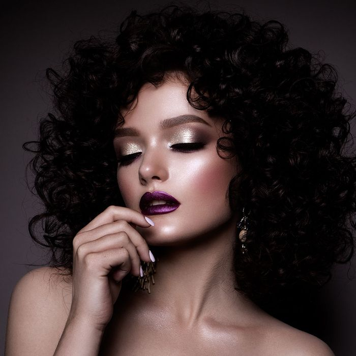 Woman with black hair, purple lipstick, and silver makeup
