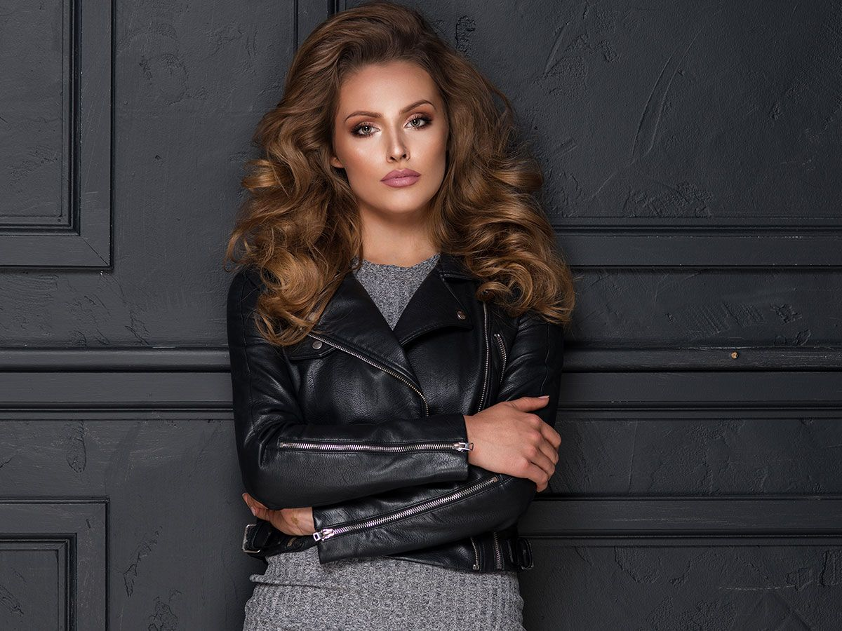 Woman in a leather jacket standing in front of a black wall