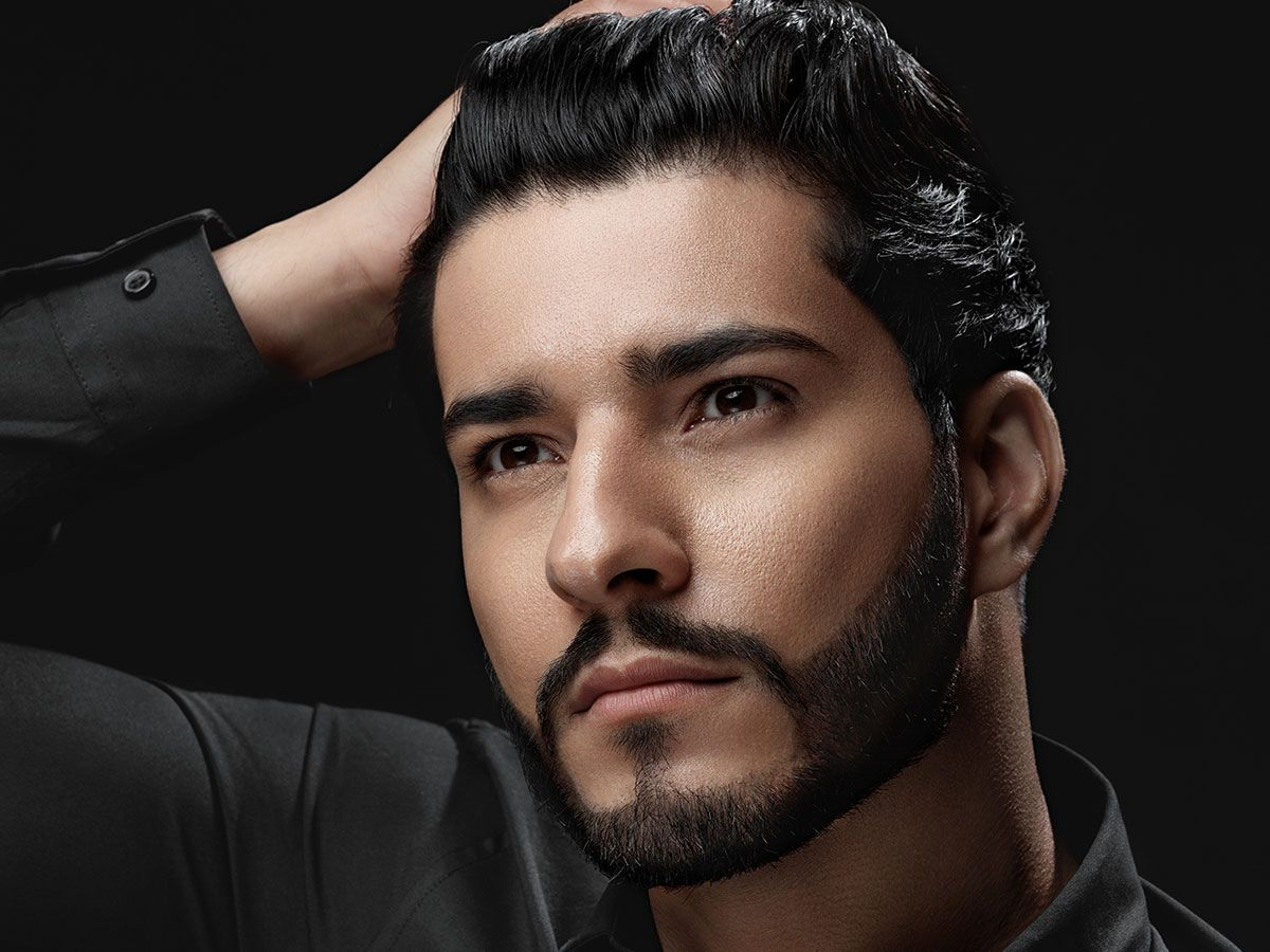 Image of a man in a black shirt touching his styled hair.