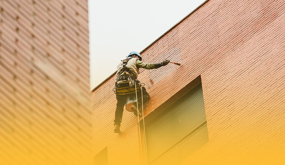 Commercial painter suspended on side of building