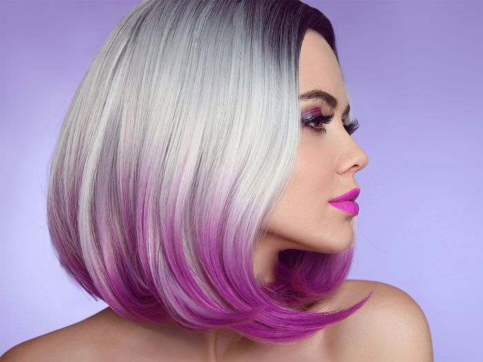 Close up profile photo of a woman wearing a blonde bob wig with ombre pink tips, curled at the ends against a purple background.