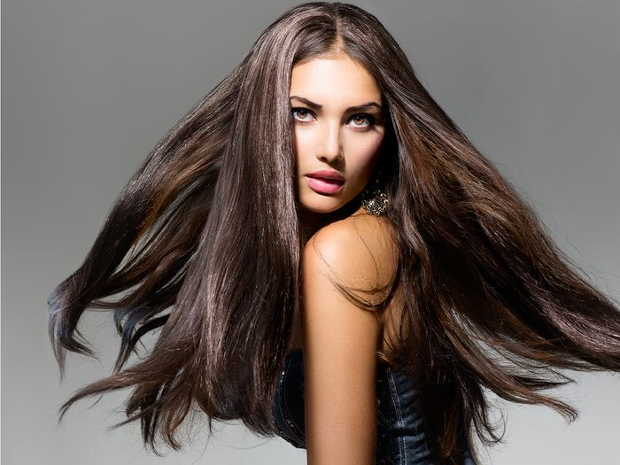 A female fashion model with long blowing hair against a dark grey background.