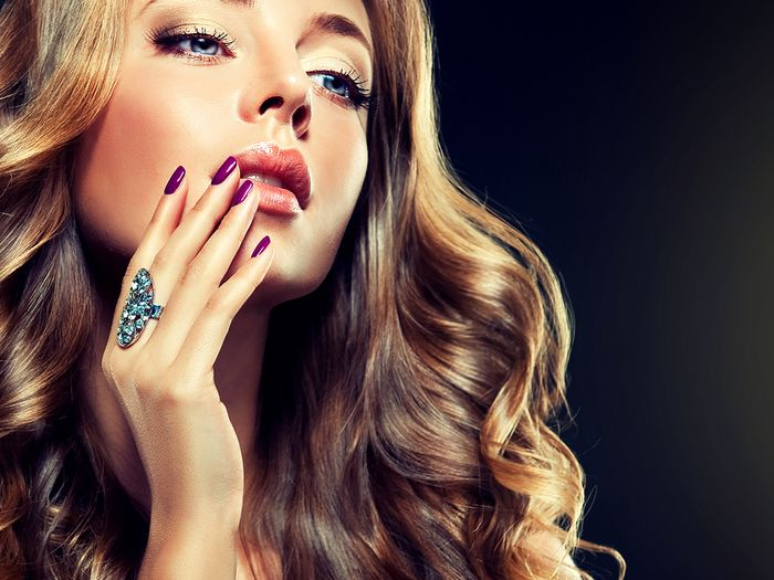 Beautiful woman holding her hand to her face with a large metal ring on her finger.