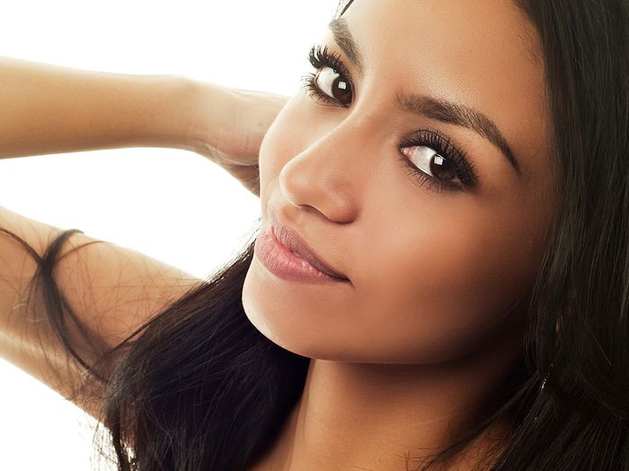 Close up portrait of a beautiful mixed race woman slightly smiling and posing with her arm behind her head.