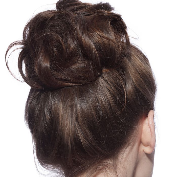 Back of brunette woman's head with a large, loose bun in her hair.