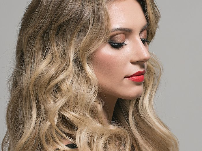 Profile view of woman with long, blonde wavy hair.