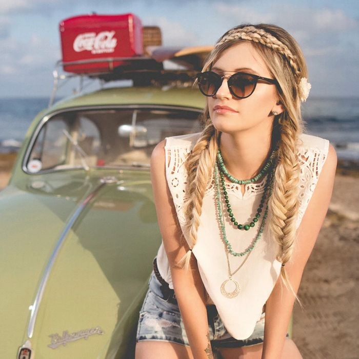 Girl with two fishtail braids sits on old, green VW bug parked on beach.