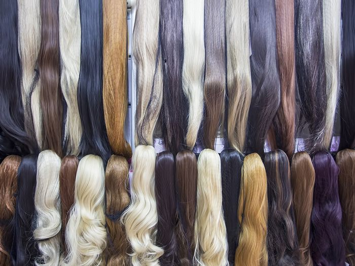 Different colors of hair extensions in a wig store.
