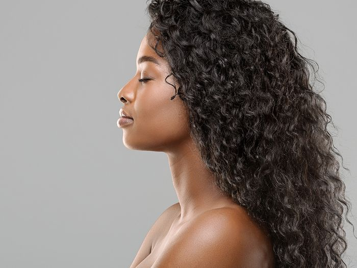 Profile portrait of beautiful African American woman with long curly hair extensions against a light gray background.