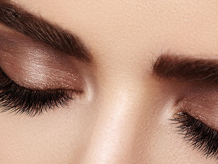 Close up of a woman's closed eyes showing her eyeshadow and long eyelashes.
