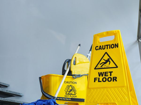Safety sign with phrase Caution wet floor and mop bucket, indoors.