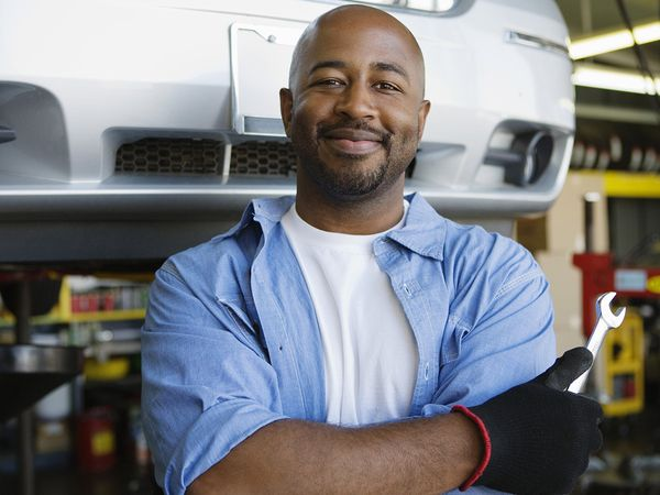 Portrait of a confident mechanic holding wrench at garage