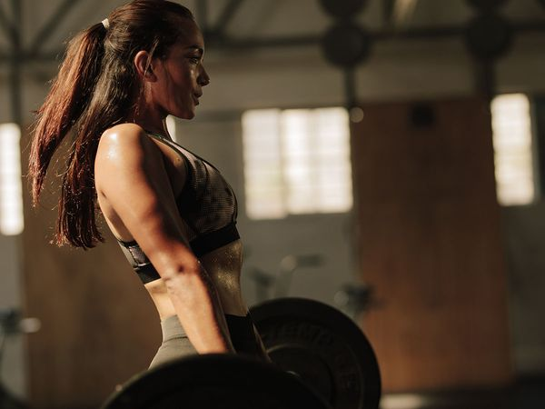 Fitness female doing heavy weight workout at gym.
