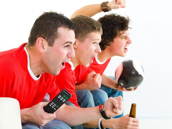 Three happy soccer fans sitting on couch and watching sport on TV