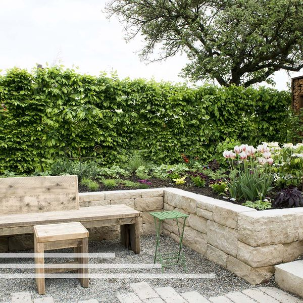 Retaining wall creating a flower bed with a bench in front of it.
