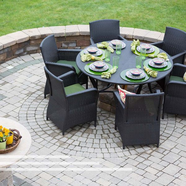 Retaining wall around a patio with outdoor kitchen and a table with chairs.
