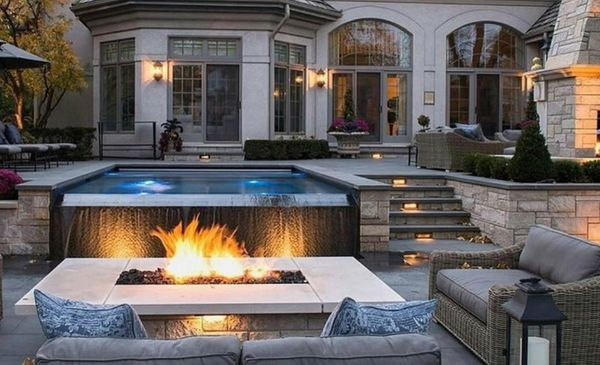 A luxury home with a custom pool, fireplace, stairs, and patio.