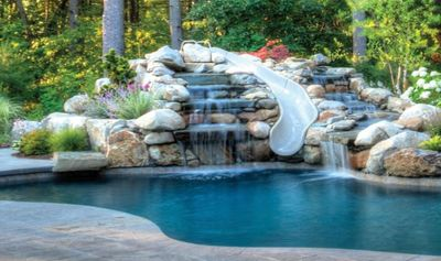 Residential pool with a water slide and water feature.