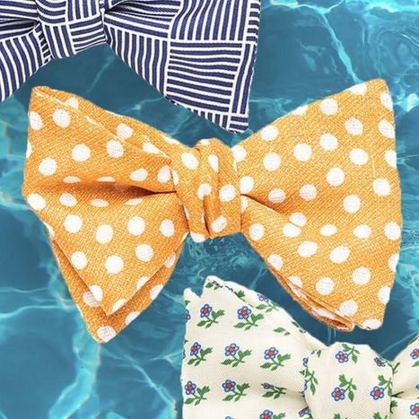 Three colorful, summery bow ties against a bright blue, watery background.