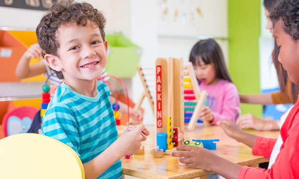 Image of a preschool aged boy smiling while learning with other children