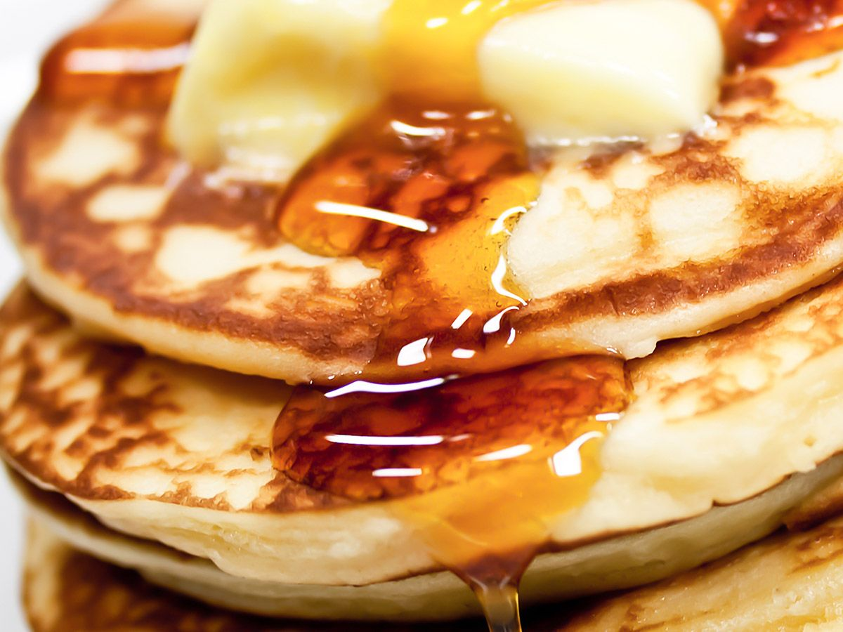 Pancakes with butter and maple syrup.