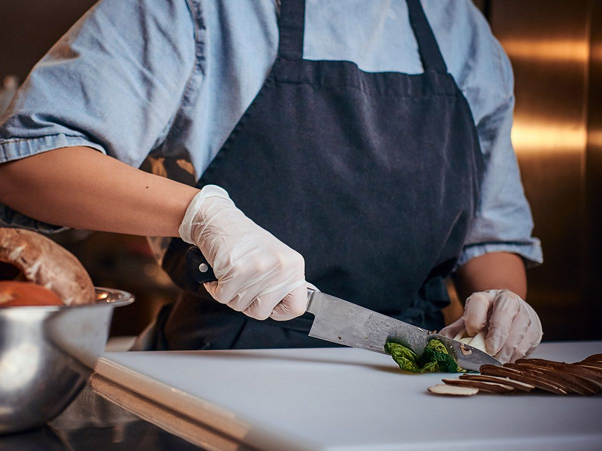 Chef standing in a kitchen and cutting vegetables on a cutting board.